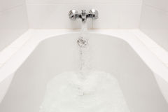Luxury bath tub and faucet with water. Royalty Free Stock Images
