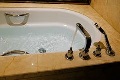 Luxury bath tub and faucet with water. Luxury bath tub and faucet with water background photo royalty free stock images