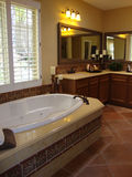 Luxury Bathroom. Beautiful luxury bathroom with dark wood cabinets and tile floors, white wood shudders Stock Photography