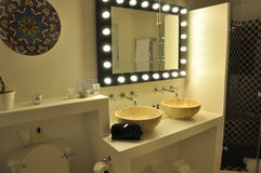 Luxury bathroom. A luxury bathroom hollywood lights with double handbasin shower and african baskets stock images