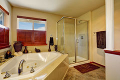 Luxury bathroom with corner bath tub and glass shower. Marble tile floor and beige walls. Northwest, USA Royalty Free Stock Photos