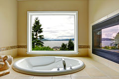 Luxury bathroom with fireplace and bay view Royalty Free Stock Photography
