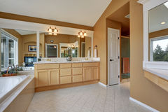 Luxury bathroom interior. Orange brown walls and vaulted ceiling. Large mirrors and double sink bathroom vanity. Northwest, USA Royalty Free Stock Photos