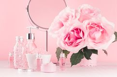 Luxury bathroom interior in romantic style - soft pink roses, cosmetic products for skin, body care, accessories, round mirror. Luxury bathroom interior in stock photos