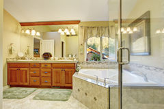 Luxury bathroom interior with tile floor. Bath tub with brown granite tile trim and vanity cabinet with large mirror Stock Photography