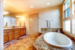 Luxury bathroom interior with tile floor. White bath tub with br Stock Images