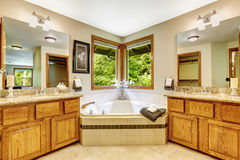 Luxury bathroom interior with two vanity cabinets and corner bat. H tub with windows. Master bedroom bahtroom Stock Photos