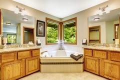 Luxury bathroom interior with two vanity cabinets and corner bat Stock Photos