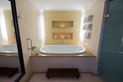 Luxury bathroom with large bath and lit candles stock photos