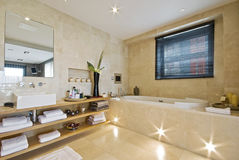 Luxury bathroom with light brown marble. Luxury en-suite bathroom with light brown marble and built in plasma tv Royalty Free Stock Photos