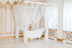 Luxury bathroom in light colors with golden furniture details and canopy. Elegant classic interior. Royalty Free Stock Photos