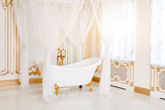 Luxury bathroom in light colors with golden furniture details and canopy. Elegant classic interior. Royalty Free Stock Photo