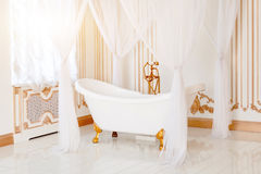 Luxury bathroom in light colors with golden furniture details and canopy. Elegant classic interior. Stock Image