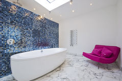 Luxury bathroom with sofa. Modern luxury bathroom with pink sofa mosaic tiles and marble floor Stock Photo