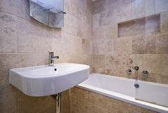 Luxury bathroom with stone tiled walls. Luxury stone tiled bathroom with large bath tub and ceramic basin Stock Photography