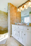 Luxury bathroom with white cabinets, marble counters, and large Royalty Free Stock Image