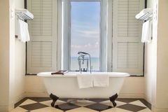 Luxury bathtub with relaxing ambient window  with scenic sea vie Stock Photos