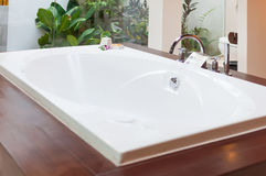 Luxury bathtub with small outdoor view Royalty Free Stock Photos