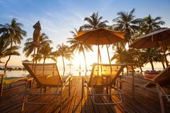 Luxury beach hotel. Two deckchairs near swimming pool at sunset in luxury beach hotel on tropical island Royalty Free Stock Photo