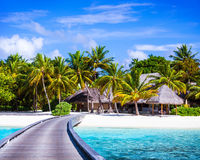Luxury beach resort. Footbridge to the paradise, little wooden houses, summer holidays, Maldives island, travel and tourism concept Stock Photos