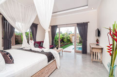Luxury and Beautiful Bedroom Villa. Beautiful interior and Bedroom villa and Hotel in Bali property with wooden bed and white netting overlooking to the pool royalty free stock photography