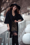 Luxury beautiful woman in black hat, trandy coat and fashion lac. E silk dress outside Royalty Free Stock Photo