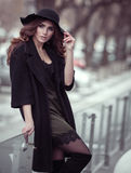 Luxury beautiful woman in black hat, trandy coat and fashion lac. E silk dress outside Stock Images