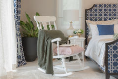 Luxury bedroom in blue color tone with white wooden rock chair Royalty Free Stock Images
