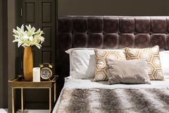 Luxury bedroom with brown color tone and flower vase and clock o Stock Photo