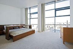 Luxury bedroom with floor to ceiling windows. And high spec furniture Stock Images
