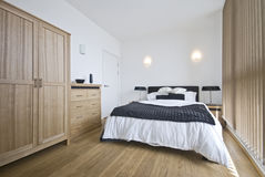 Luxury bedroom with a king size bed. Luxury double bedroom with a king size bed, wooden wardrobe and chest of drawers in beige Stock Photography