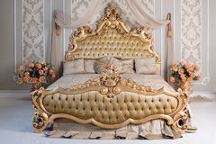 Luxury bedroom in light colors with golden furniture details. Big comfortable double royal bed in elegant classic Royalty Free Stock Photos