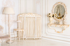 Luxury bedroom in light colors with mirror and folding screen. Elegant classic interior Royalty Free Stock Image