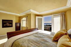 Luxury bedroom with walkout deck and fireplace royalty free stock image