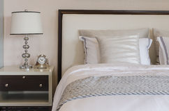 Luxury bedroom with white classic lamp and clock on table. At home royalty free stock photo