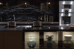 Luxury Bespoke Kitchen. Expensive and Well-Appointment Kitchen with Black Marble Royalty Free Stock Photography