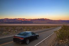 Luxury black fast American car driving on desert highway in Death Valley California, road trip, colourful sunrise mountains view stock photos