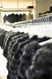Luxury fur coats hanging on rack. Luxury black fur coats hanging on rack stock photo