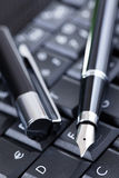 Luxury black pen on computer keyboard Stock Image