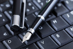Luxury black pen on computer keyboard Stock Images
