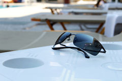 Luxury black sunglasses at the hotel swimming pool. Photo of luxury black sunglasses at the hotel swimming pool royalty free stock photos