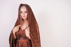 Luxury blonde caucasian model girl in chocolate color long evening dress made of pleated fabric waving a flying dress and stands o. N a white Studio background stock photography