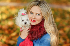 Luxury blonde girl with beautiful hair in autumn coat holding a. Small dog in her arms, close-up stock images