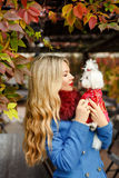Luxury blonde girl with beautiful hair in a coat in autumn park. Holding a small dog in her arms royalty free stock images