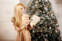 Luxury blonde in interior New Year. Young beauty trendy girl cel Stock Photography