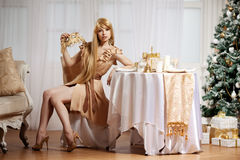 Luxury blonde in interior New Year. Young beauty trendy girl cel Royalty Free Stock Photo