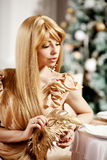 Luxury blonde in interior New Year. Young beauty trendy girl cel Royalty Free Stock Images