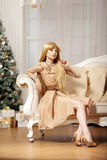 Luxury blonde in interior New Year. Young beauty trendy girl cel Royalty Free Stock Photos