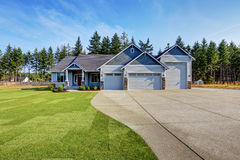 Luxury blue house with curb appeal. Three car garage. Luxury blue house with curb appeal. Three car garage and long, wide asphalt driveway. Northwest, USA Royalty Free Stock Photography