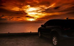 Luxury blue SUV car parked on concrete road by the sea at sunset with dramatic sky and clouds. Electric car technology and busines. S. Hybrid auto and automotive stock photos